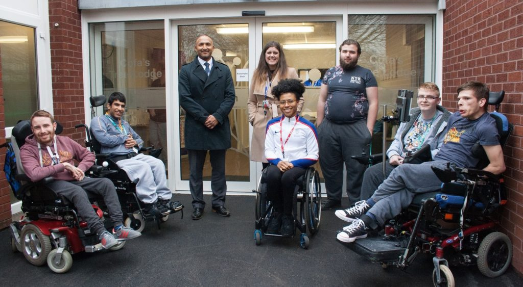 Karen Adenegan outside newly established living space at Hereward college with some of the students