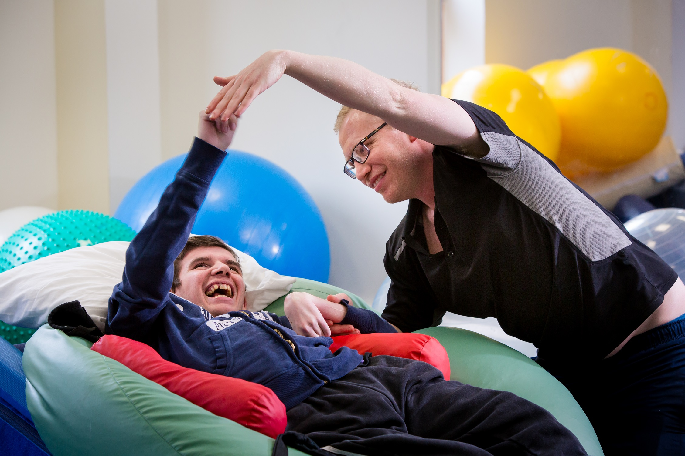 A student having a physiotherapy session raising his arm above his head