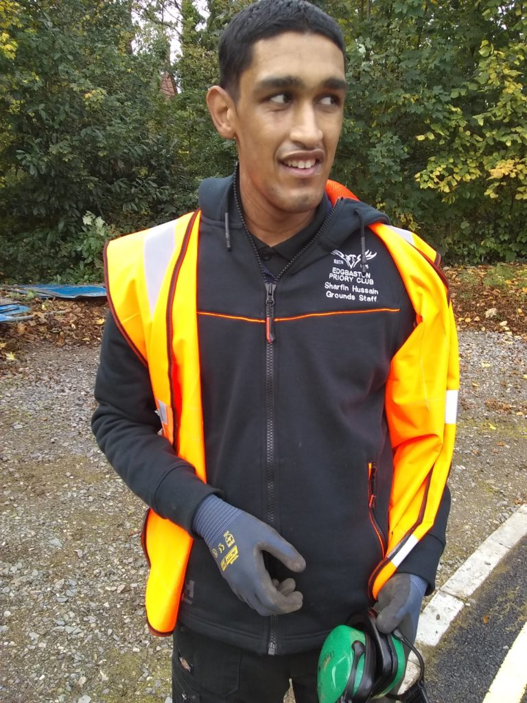 Sharfin in his work uniform, including a high-vis vest, holding a pair of ear defenders