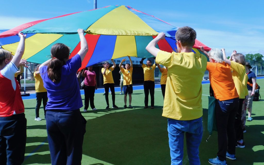 Students engage in a parachute game at the Natspec Games