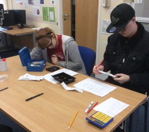 two students helping with accounts work