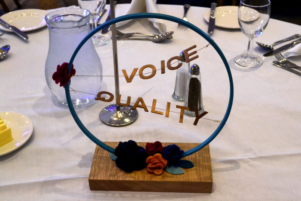 Table decoration with flowers and words 'voice and quality'
