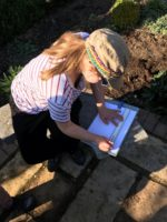 Student measuring size of flower beds