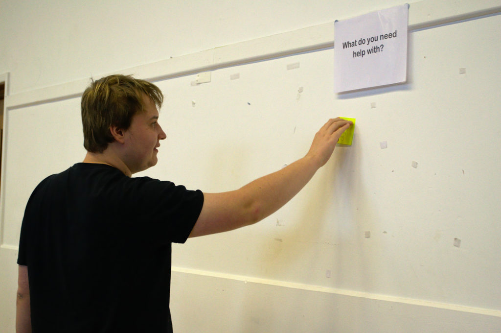 student adds first post-it note to wall