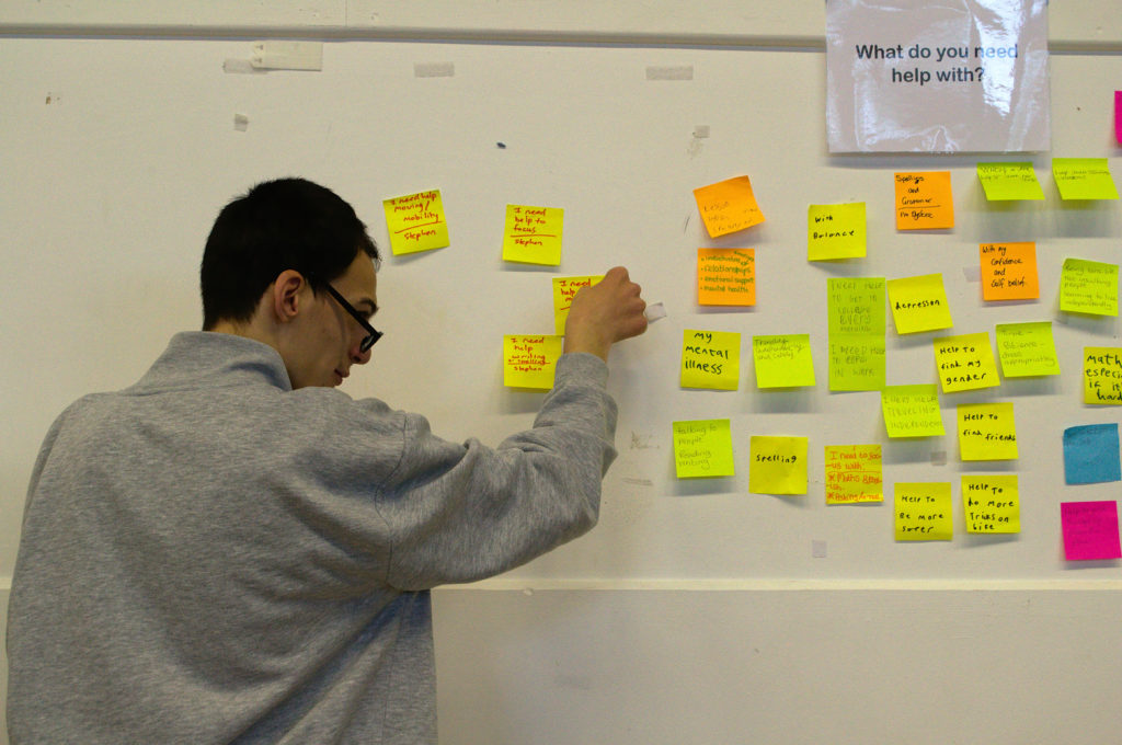 Student adding post-it note to busy wall