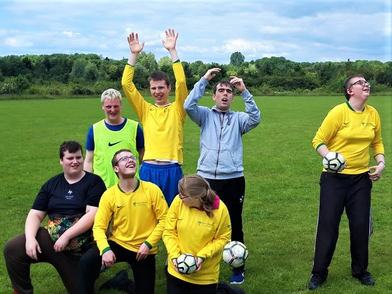 Students celebrating on a field in football kit