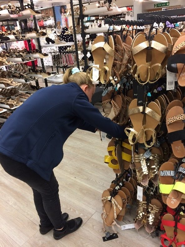 Tay arranging a display of shoes