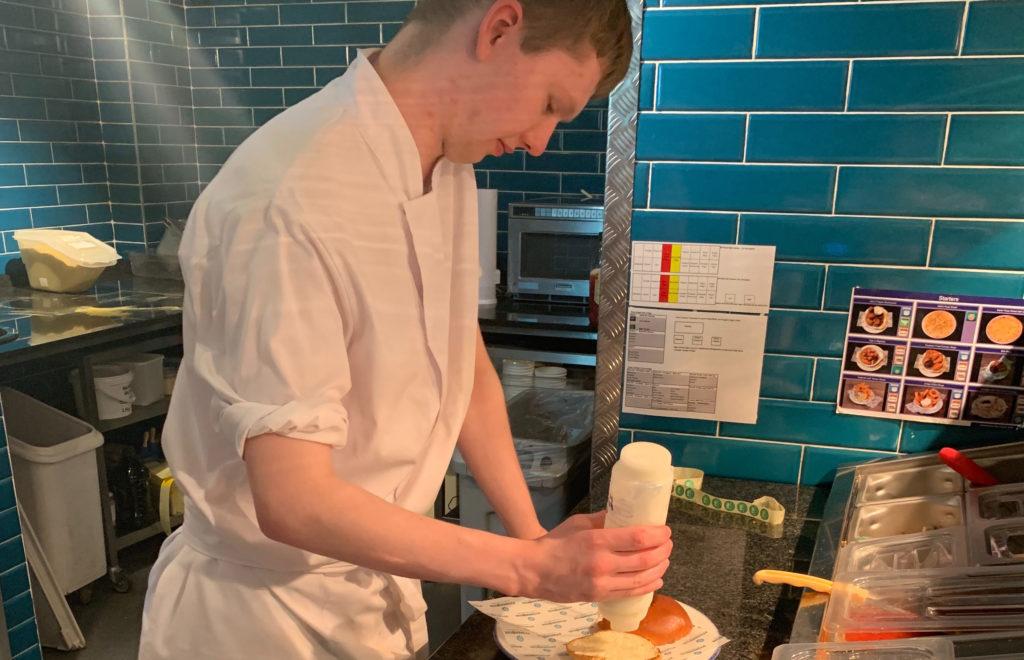 Lewis preparing a burger in the pub kitchen