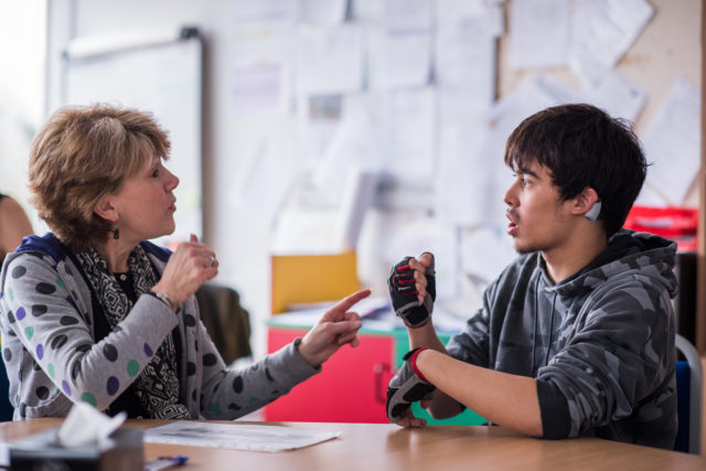 A staff member communicating with a deaf student