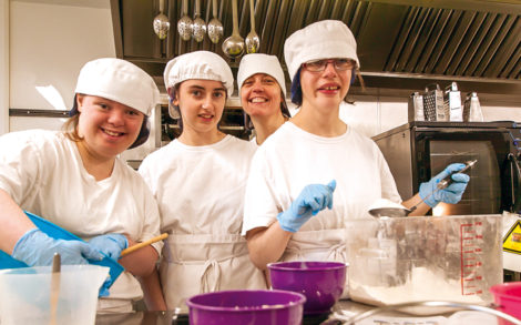 Four students in chefs whites baking cakes