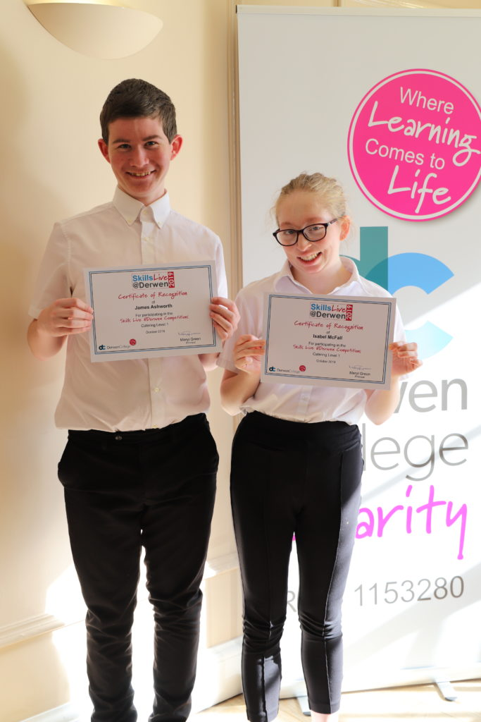 Two catering students with their certificates of recognition