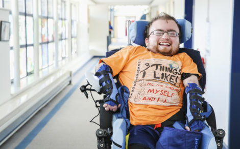 Smiling Treloar College student learning to navigate his wheelchair independently
