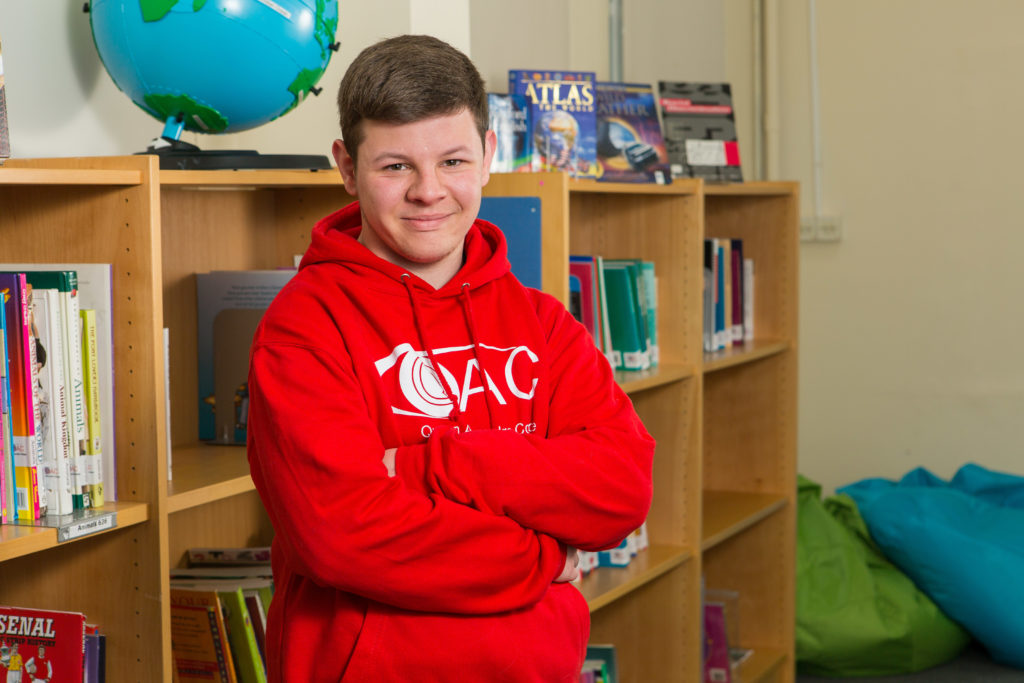 A student in a QAC hoodie standing with his arms folded in QAC's college library