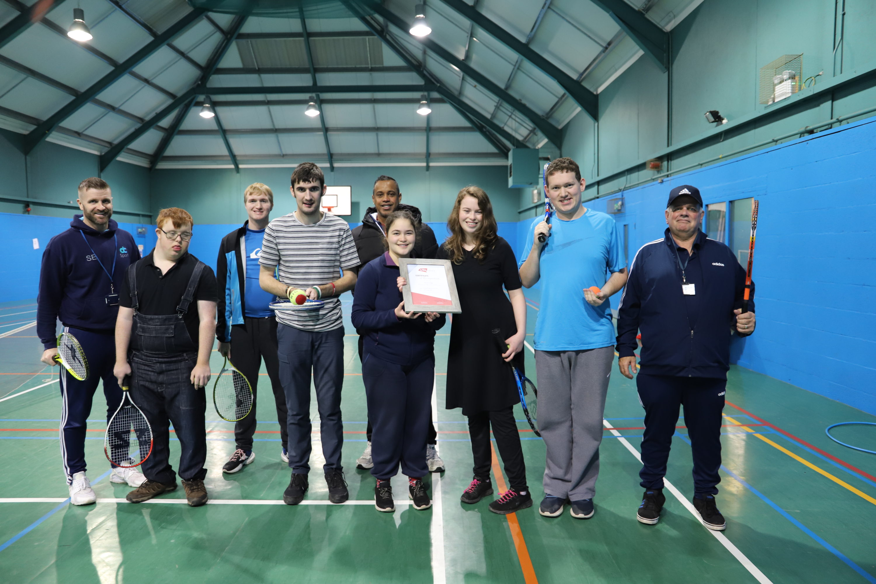 Students from Derwen in their sports hall with tennis rackets and their tennis certificate