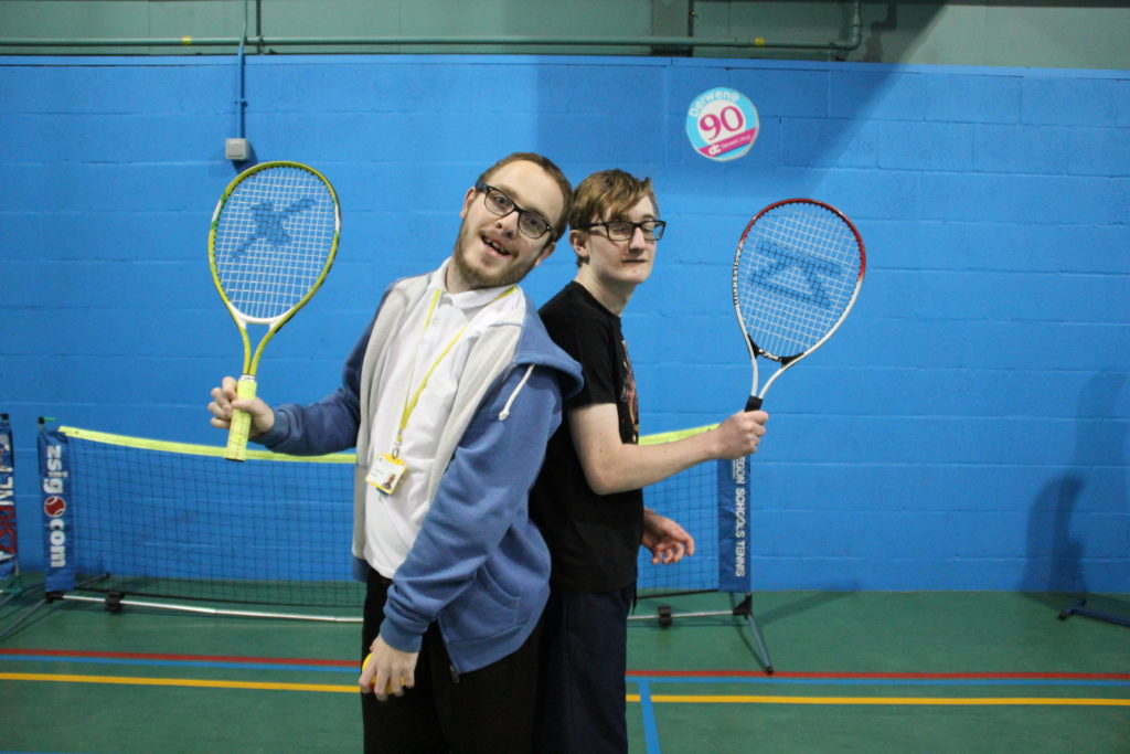 Two students showing off their tennis rackets