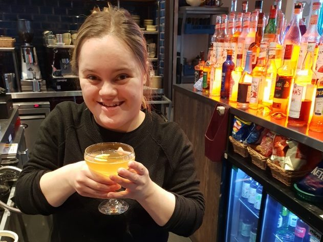 Emily holding a drink behind the bar and smiling