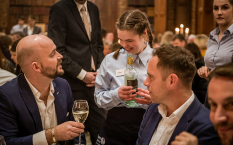 A student serving wine to a guest at a fancy event