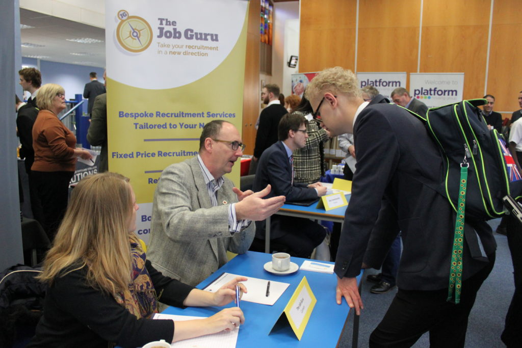 A student talks to a man who is explaining something as part of the careers fair