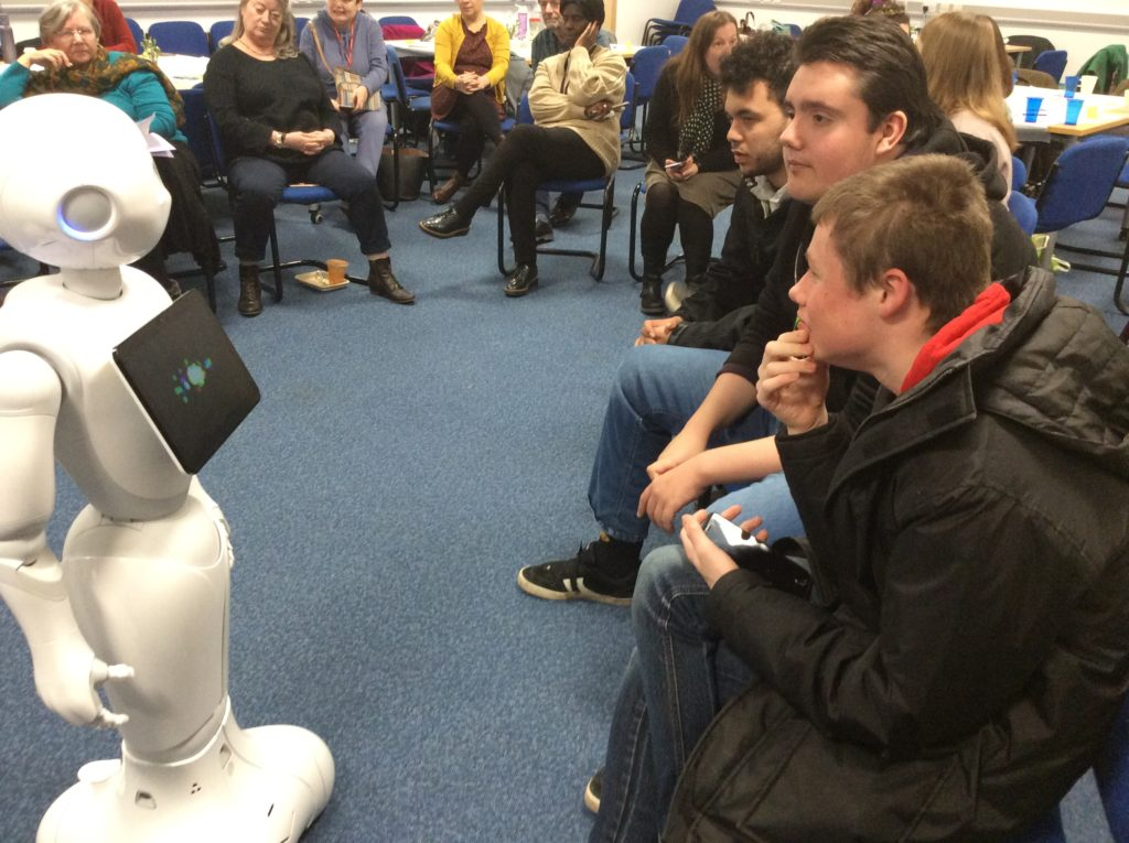 a group of students interacting with peppa the robot
