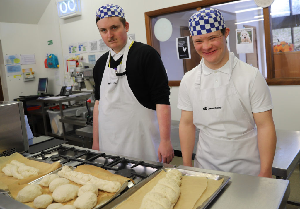 Two students in the kitchen with their loaves of uncooked bread