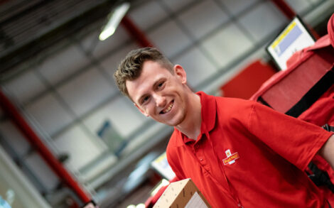 A student smiling whilst wearing a red, royal mail polo shirt