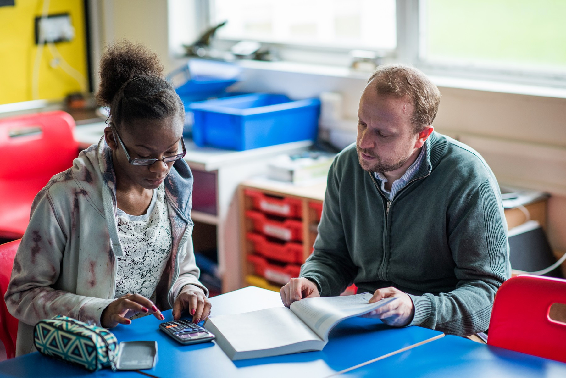 A tutor goes over some work with a learner