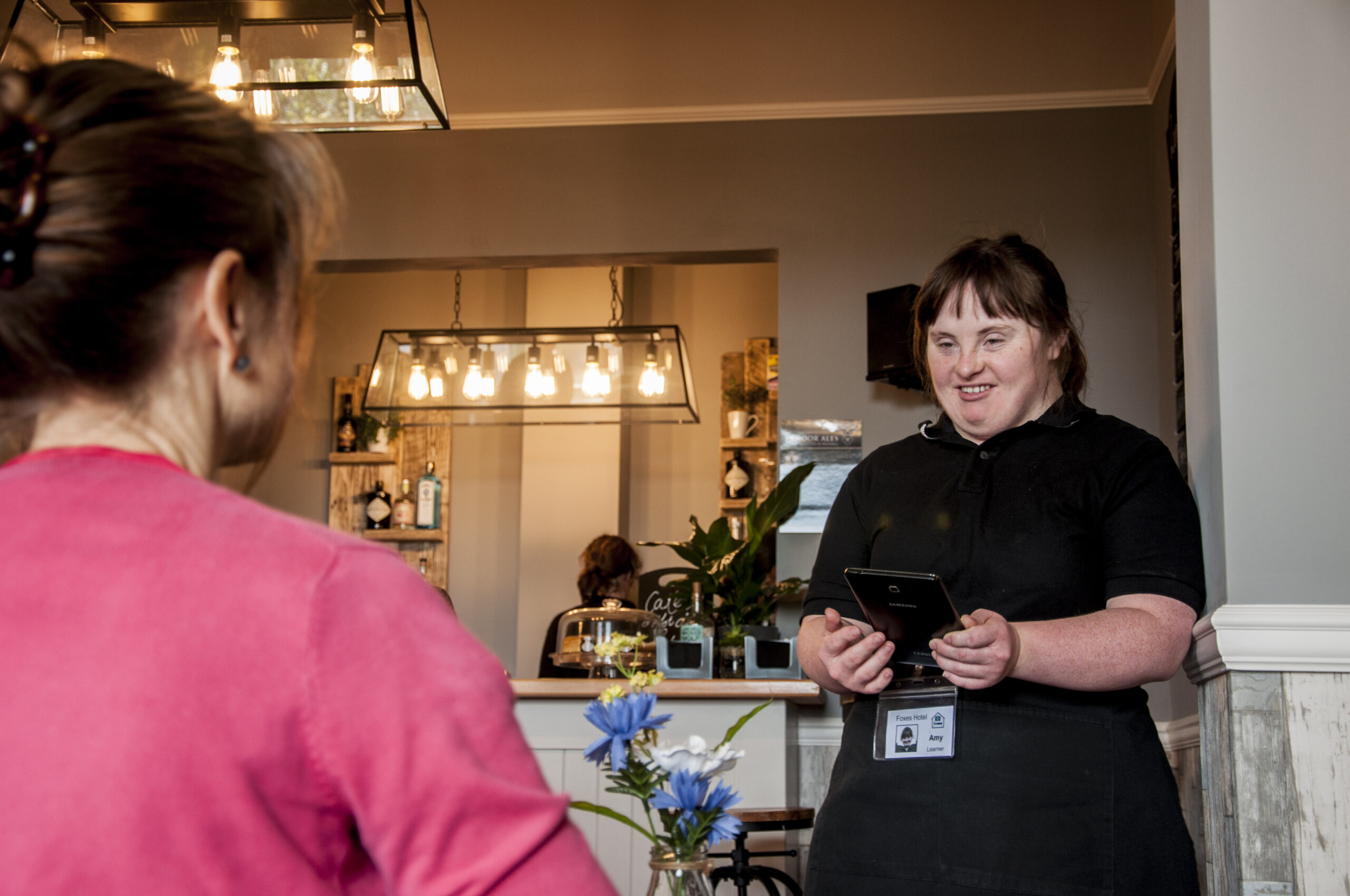 Amy, a student at Foxes, takes an order in Foxes' hotel restaurant on a tablet. She is smartly dressed in her uniform