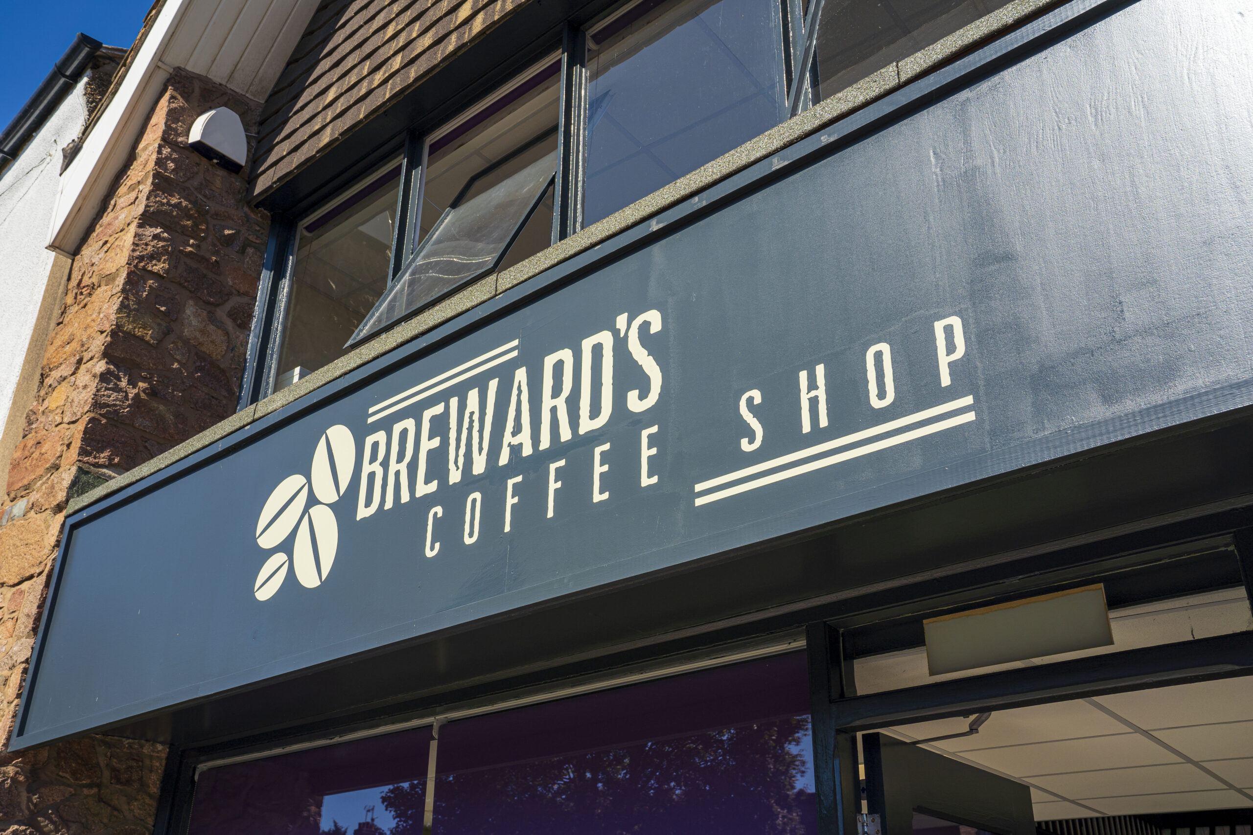 The front signage of Breward's, with the typography reading 'Breward's Coffee Shop' in white on a black background