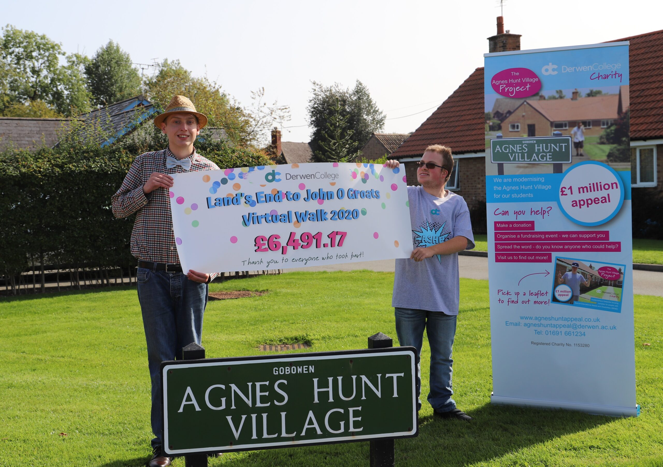Two Derwen Students holds up a sign declaring £6491.17 was raised as part of the Virtual Walk fundraising. They are standing outside Agnes Hunt Village
