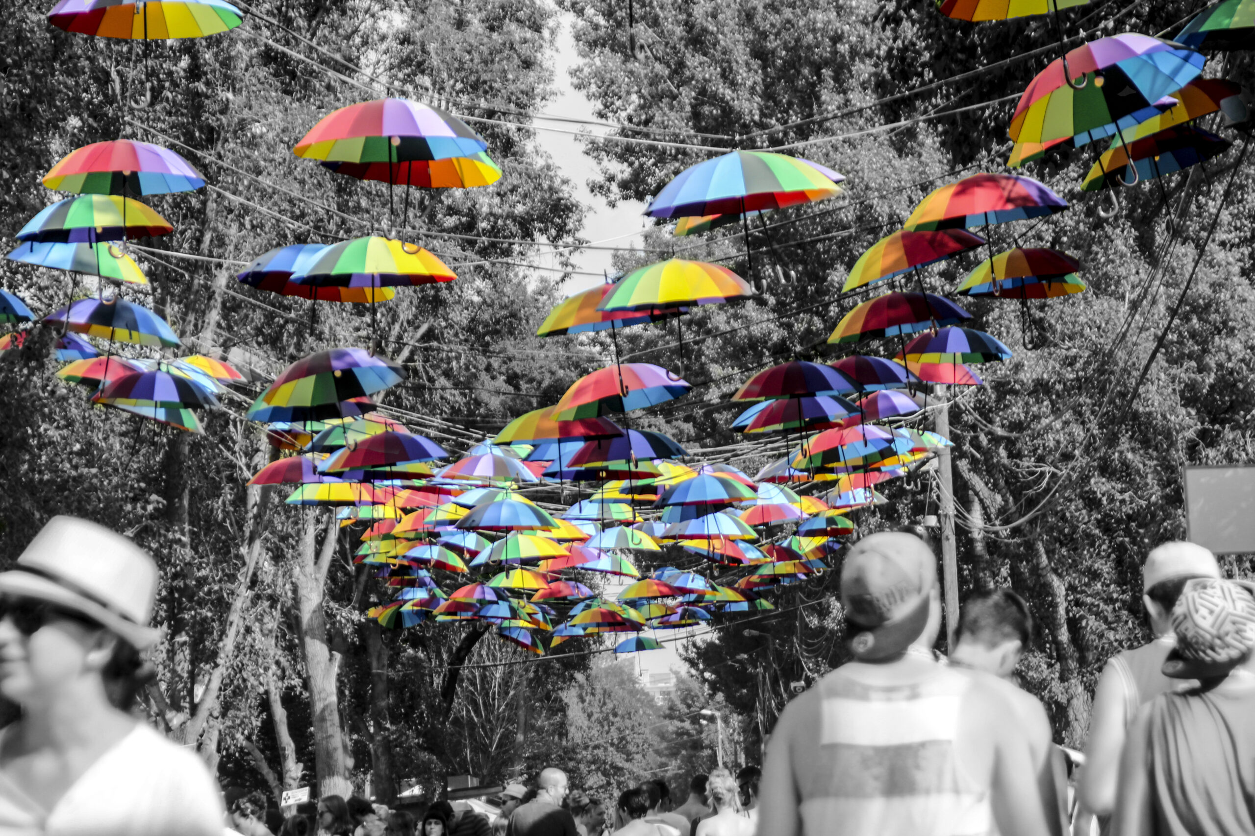 A piece of artwork by Eoin; bright multi-coloured umbrellas hand like lanterns above a black and white street scene