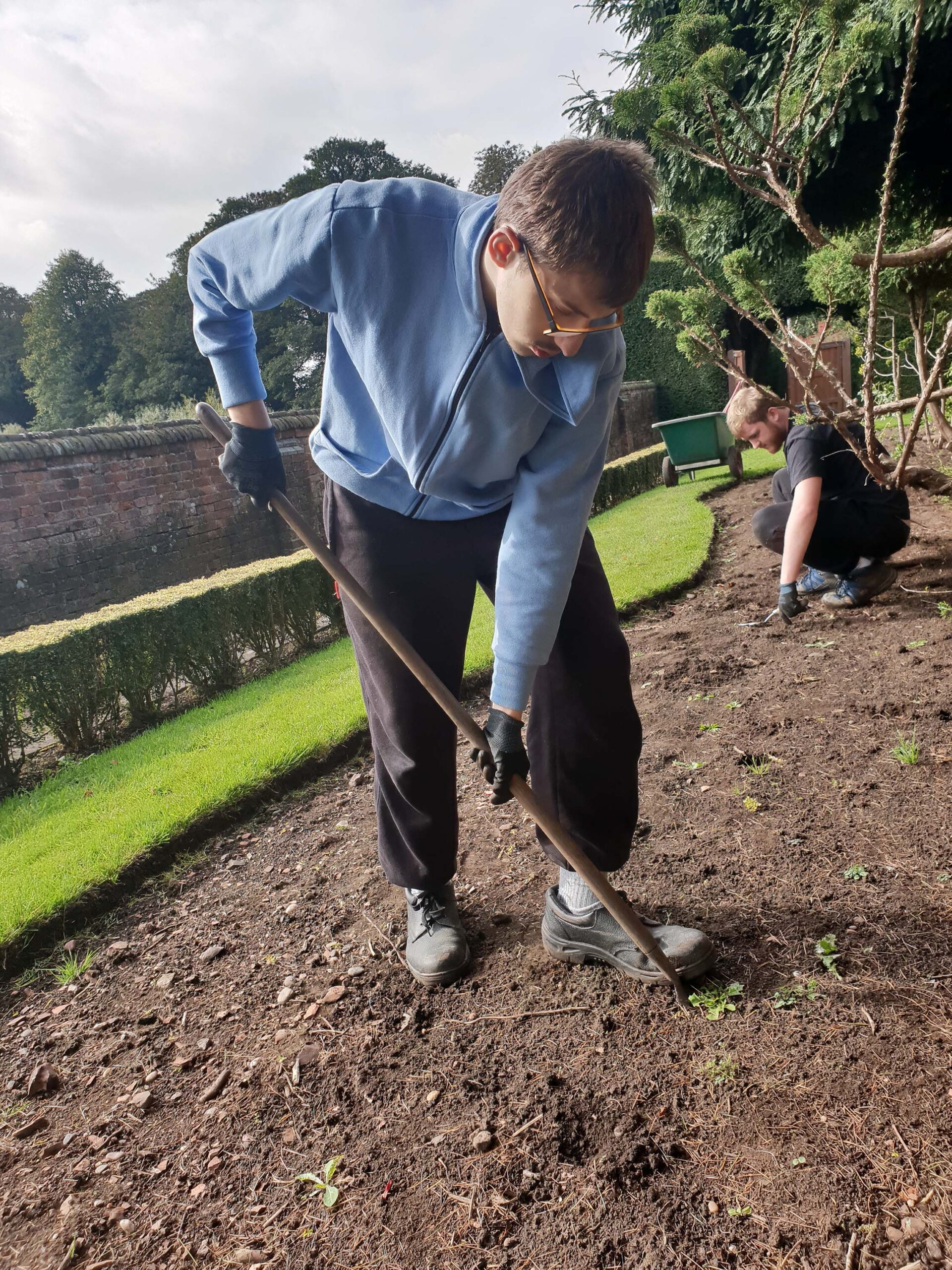 A learner uses a spade to dig in the ground during landscaping work