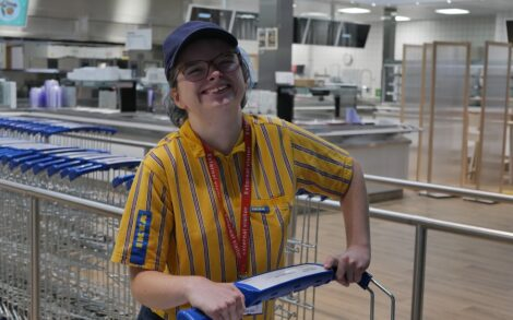 Nina smiles whilst wearing her Ikea work uniform and pushing a trolley