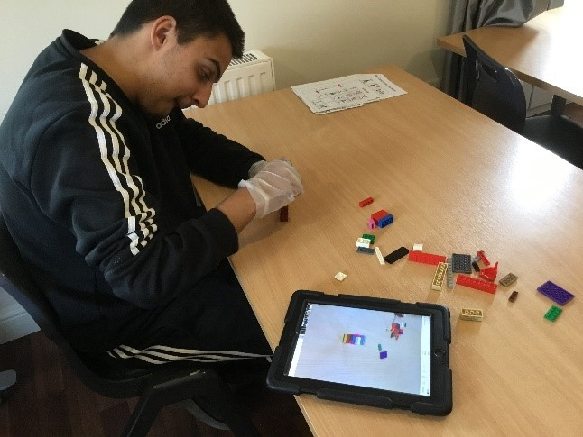 a student constructs a model from lego bricks following instructions on an iPad
