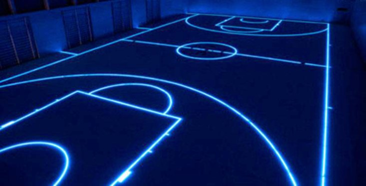 a lit up floor displaying the outline of a basketball court