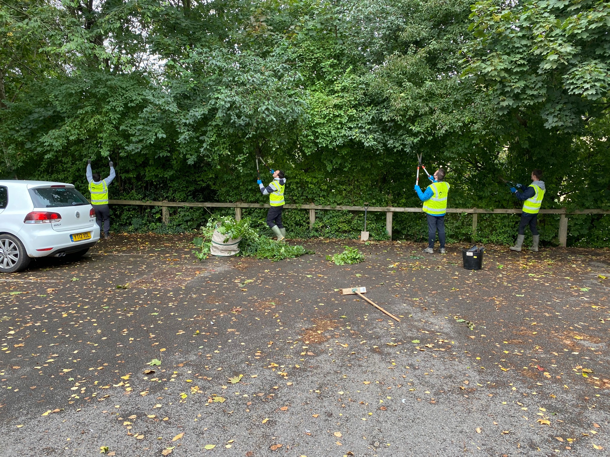 a group of students trim trees using secateurs in high vis vests