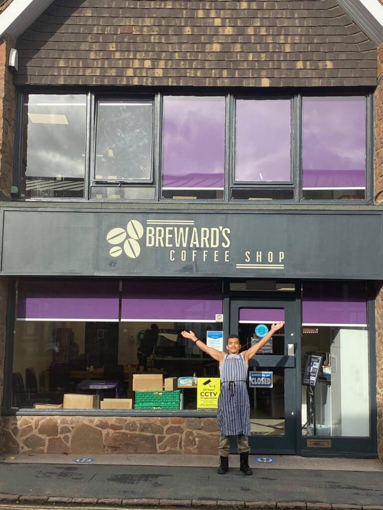 a student stands with arms held wide outside of Brewards, a coffee shop with dark signage