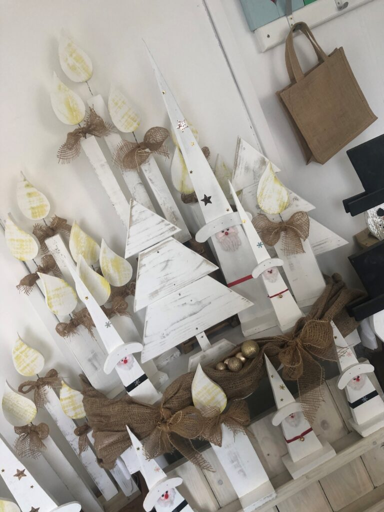 multiple wooden christmas decorations, including candles trees and father christmases, all painted white