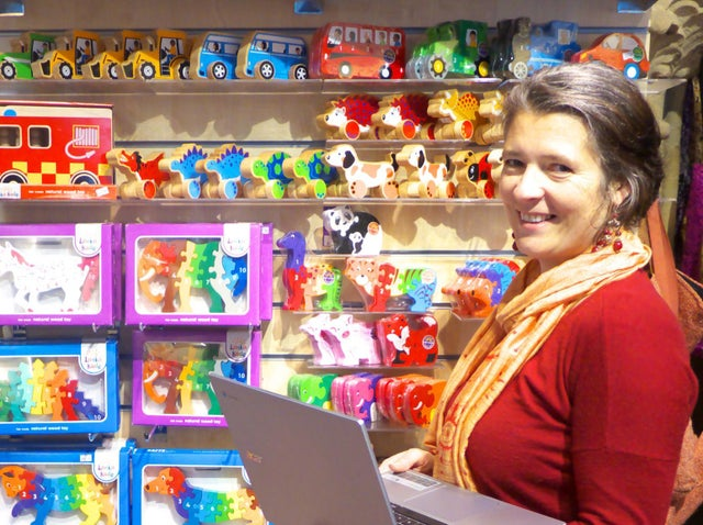 A smiling woman in front of shelves of toys