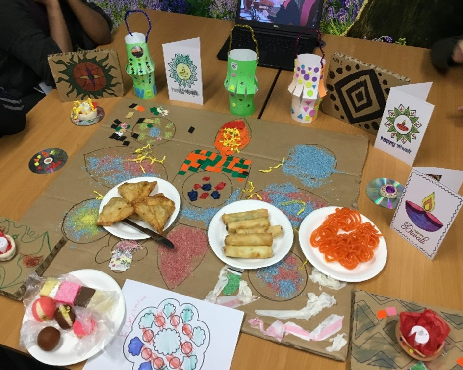 a selection of foods, cards, and rangoli patterns for diwali on a table