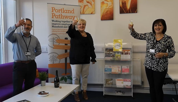 three members of staff at Portland celebrate with champagne