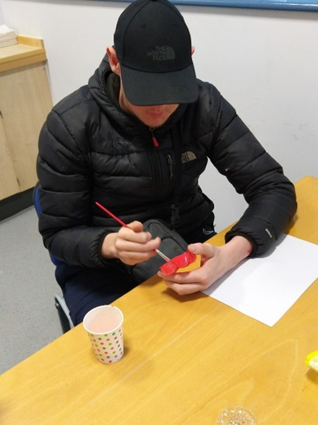 a student sitting at a desk painting a small object red