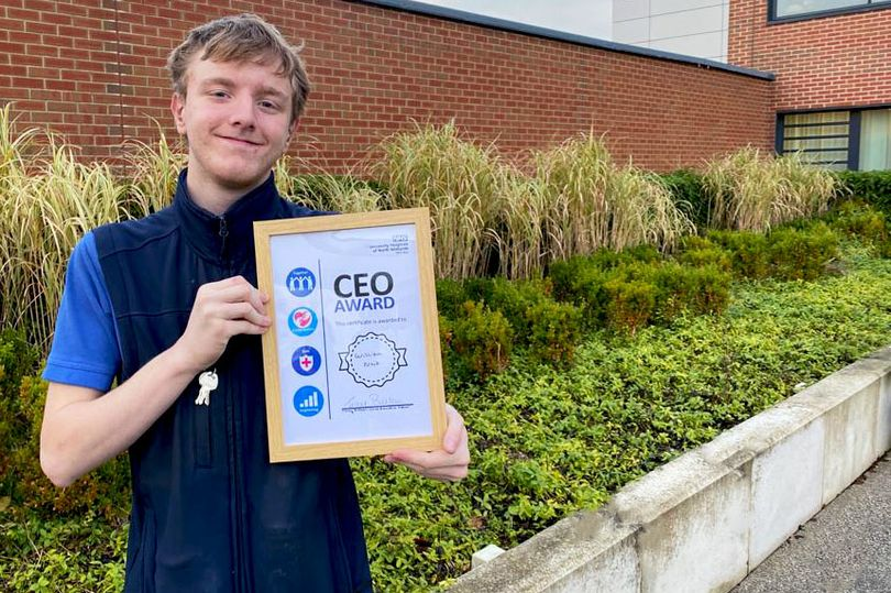 William with his chief executive award certificate, framed, smiling outside the hospital building