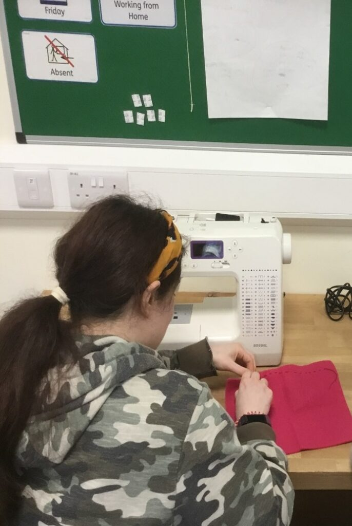 a hbvc student uses a sewing machine to stitch some pink fabric