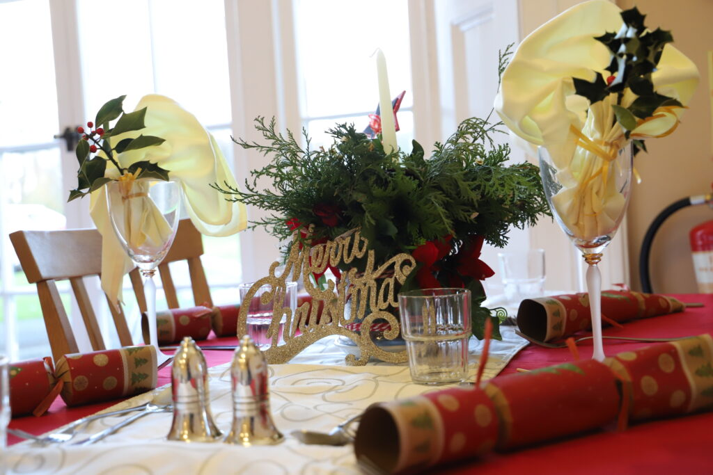 a beautifully laid out table, with christmas crackers, a glittery sign saying 'merry christmas' and holly sprigs and napkins in the glasses