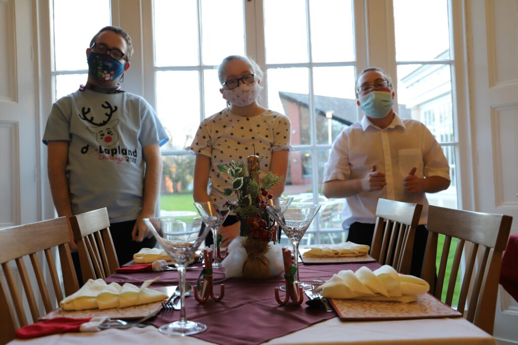 Joe, Isobel and William standing behind their table. All three are wearing face coverings
