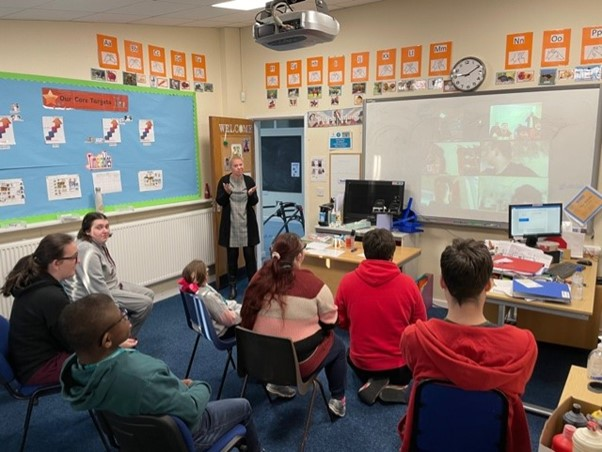 Students sitting distanced in a classroom environment are joined by students on a zoom call for a collective session