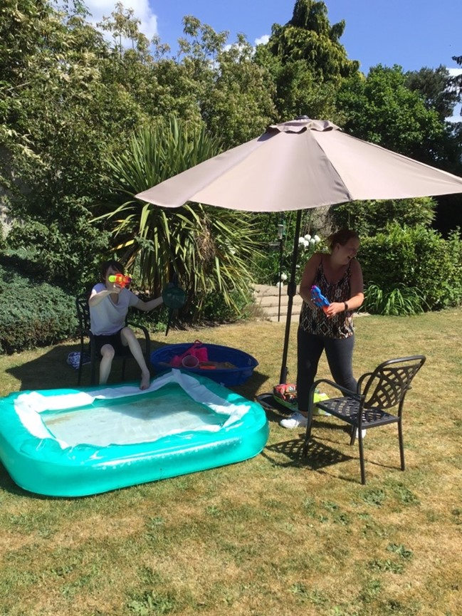 Sophie enjoys a water fight in a garden under the shade with a paddling pool