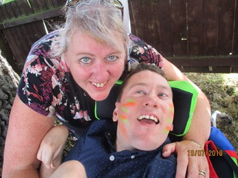 Bev, smiling, with student Matthew who is in a wheelchair with stripes of bright paint on his face