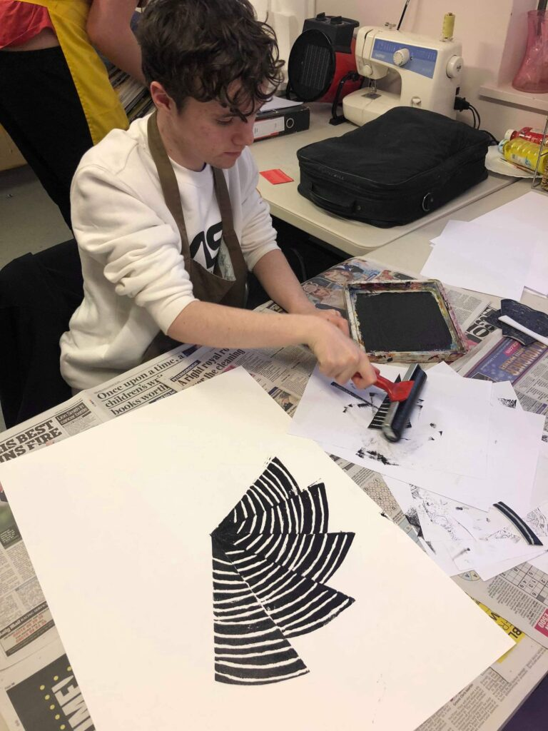 John participating in an art class, making a pretty striped circular black and white print with a roller and ink