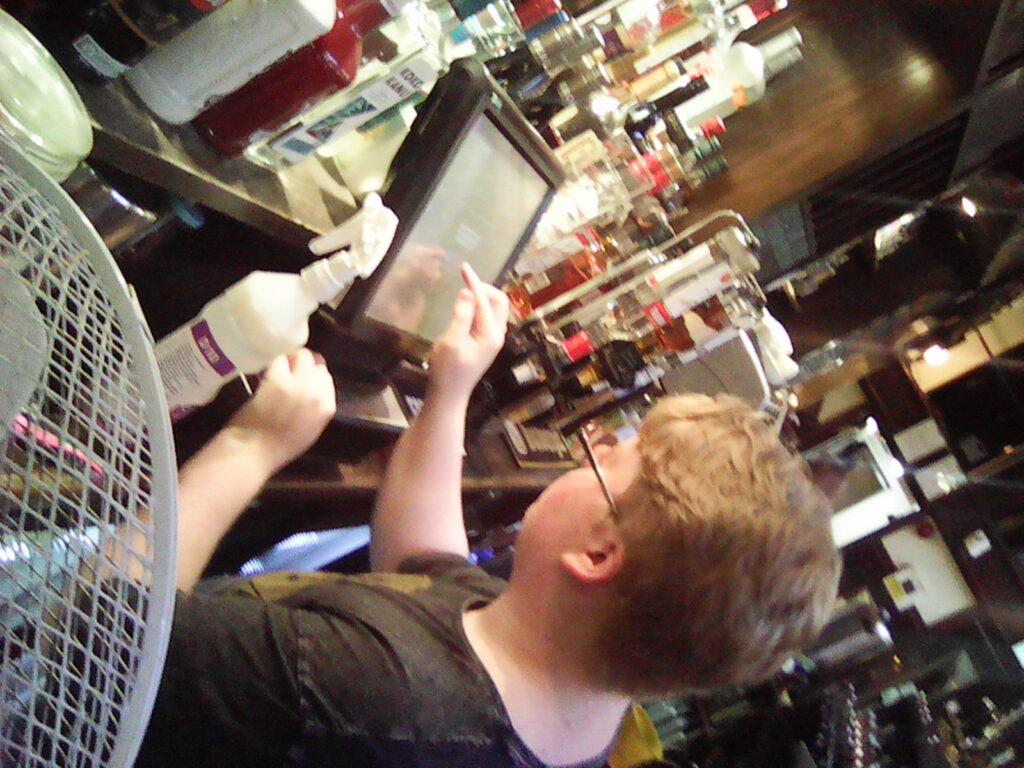 Matthew operates a touch screen till behind a bar